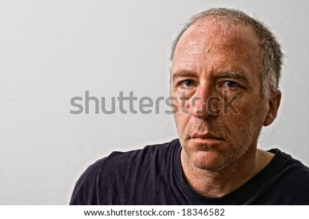 beautifully detailed real portrait of haggared tired looking adult white man looking intensely at the viewer - stock photo