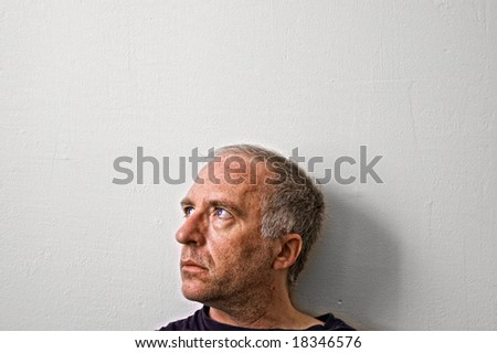 beautifully detailed real portrait of tired looking adult white man staring intensely out window with big blue eyes - stock photo