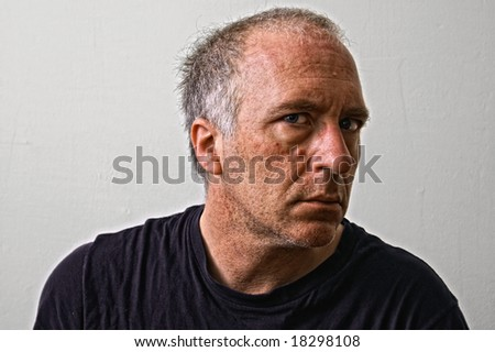 beautifully detailed real portrait of weathered looking adult white man staring intensely at the viewer with head turned away - stock photo