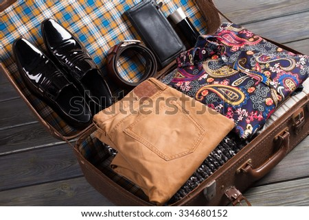 Beautifully folded clothes for travel. Suitcase of traveler. - stock photo
