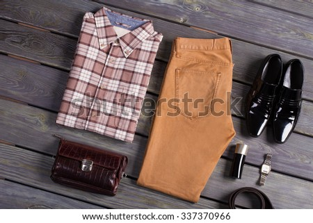 Beautifully folded men's clothing lying on a wooden floor. - stock photo