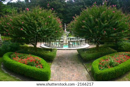 Beautifully landscaped garden with a center fountain - stock photo