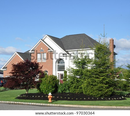 Beautifully Landscaped Suburban Home with Japanese Maple Tree Evergreen Trees - stock photo