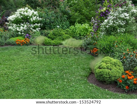 Beautifully landscaped summer garden with green lawn. - stock photo