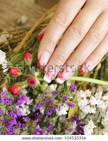 Beautifully manicured fingernails with flowers in the background