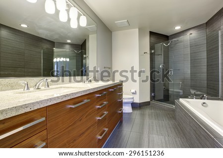 Beautifully modernized bathroom with gray flooring and large glass shower. - stock photo