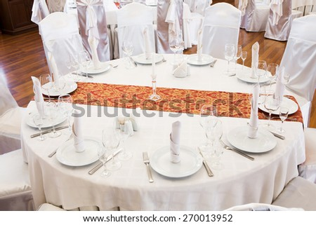 Beautifully organized event - served festive round table in luxurious interior - stock photo