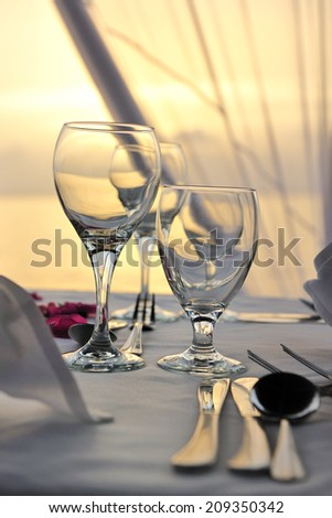 beautifully served table by the beach with sunset - stock photo