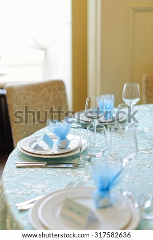 Beautifully served table in a restaurant / Beautiful holiday table setting in white and blue color with a gift on the plate - stock photo
