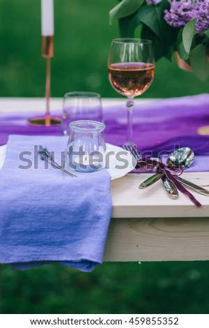 beautifully served table outdoor with flowers and decor - stock photo