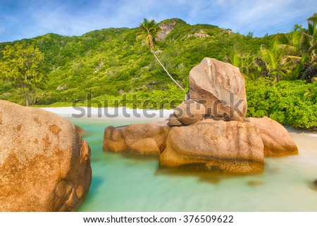 Beautifully shaped granite boulders in the turquoise sea (daytime long exposure technique) and a perfect white sand at Anse Coco, La Digue island, Seychelles - stock photo