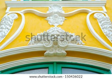 Beautifully Stucco facade windows.on yellow wall - stock photo