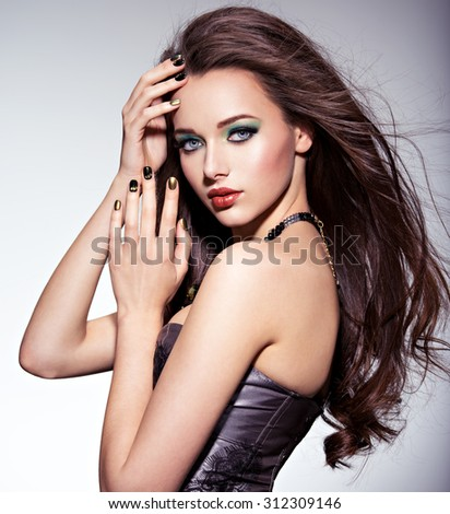Beautiul woman with long brown hairs and green make-up and   nails - stock photo