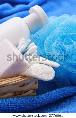 beauty accessories - soap bottle of shampoo in basket on blue towel