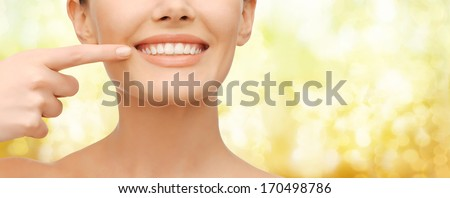 beauty and dental health concept - closeup picture of beautiful woman pointing finger to her teeth - stock photo