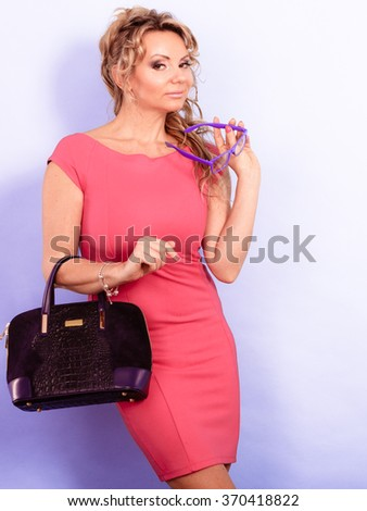 Beauty and fashion. Middle aged fashionable woman wearing pink red dress holds handbag purse bag and eyeglasses, studio shot on violet - stock photo