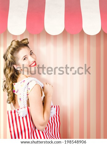 Beauty and fashion portrait of a beautiful blond woman with pinup hair style carrying shopping bag on pink stripe salon wall. Cosmetic and hairdresser copyspace - stock photo