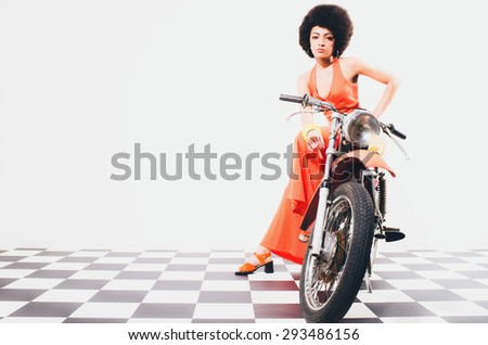 Beauty and glamour portrait of an elegant lady with an afro hairstyle posing full length on a motorbike in a long orange dress over a checkered black and white floor - stock photo