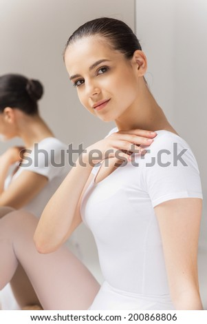 Beauty and grace. Beautiful young ballerina touching her shoulder and looking at camera while sitting near the mirror - stock photo