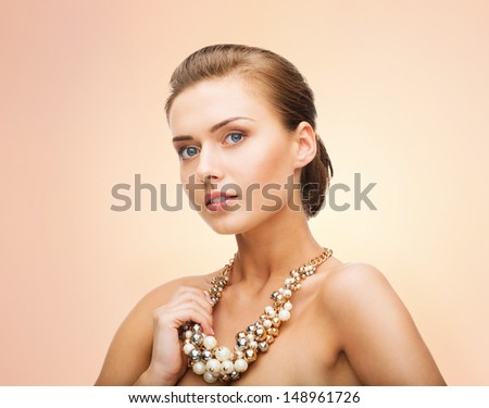 beauty and jewelery concept - beautiful woman wearing statement necklace with pearls - stock photo