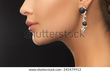 beauty and jewelery concept - woman wearing shiny diamond earrings - stock photo
