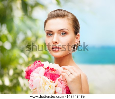 beauty and jewelry concept - woman wearing earrings, ring and holding flowers - stock photo
