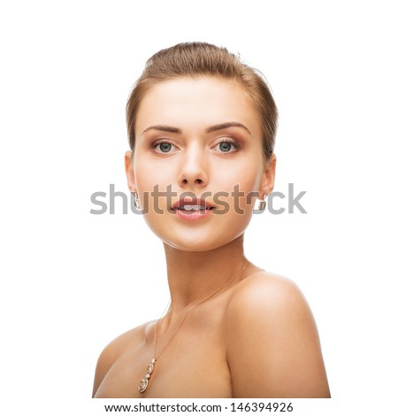 beauty and jewelry concept - woman wearing shiny diamond earrings