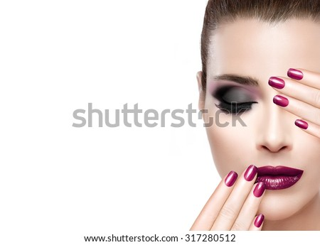 Beauty and Makeup concept. Fashion model woman with hands on face covering half mouth and one eye. Perfect skin. Festive manicure and makeup. High fashion portrait isolated on white with copy space. - stock photo