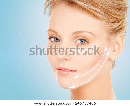 beauty and people concept - face of beautiful young woman over blue background - stock photo