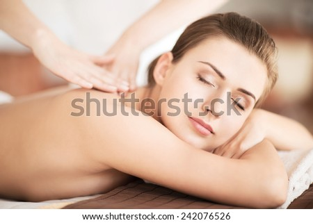 beauty and spa concept - beautiful woman in spa salon getting massage - stock photo