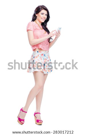 Beauty and technology. Full length of beautiful young fashionable woman using smartphone. Isolated on white. - stock photo