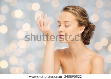 beauty, aroma, people and body care concept - young woman smelling perfume from wrist of her hand over holidays lights background - stock photo