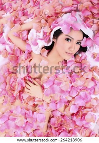 beauty asian girk model in flower petals  - stock photo