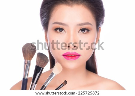 Beauty Asian Girl with Makeup Brushes. Natural Make-up for Asian Woman with Brown Eyes. Beautiful Face. Makeover. Perfect Skin. Applying Makeup - stock photo