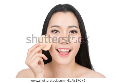 Beauty asian woman applying makeup with Sponge Powder Puff. Beautiful asian woman face and Perfect skin. keep pore details.