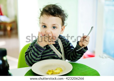 Beauty baby boy eating food with a spoon, toddler eating messy and getting dirty - stock photo