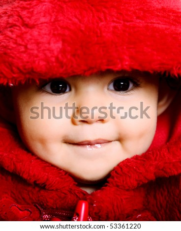Beauty baby looking at the camera with red hood - stock photo
