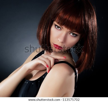 Beauty. Beautiful red hair woman in wig over dark background indicating her finger backwards