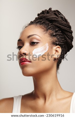 beauty black woman with a cream on her cheek - stock photo