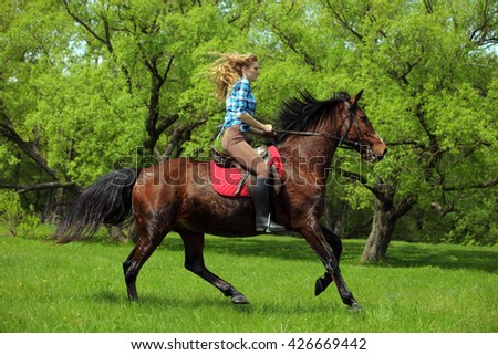 Beauty blond girl riding horse in woods
