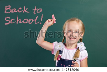 beauty blond little girl holding chalk, standing near chalkboard