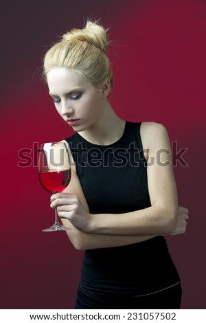 beauty blond model holding wineglass with red wine  - stock photo