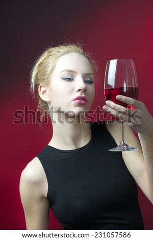 beauty blond model holding wineglass with red wine lookind into glass  - stock photo