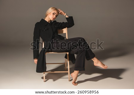 Beauty blond woman  in a black coat on chair on a gray background