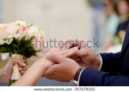 Beauty bride and handsome groom are wearing rings each other. Wedding couple on the marriage ceremony. Beautiful model girl in white dress. Man in suit. Female and male portrait. Cute lady and guy - stock photo