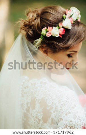 Beauty bride in bridal gown with bouquet on the nature. Beautiful model girl in a white wedding dress and wreath of flowers. Female portrait in the park. Woman with hairstyle.  - stock photo