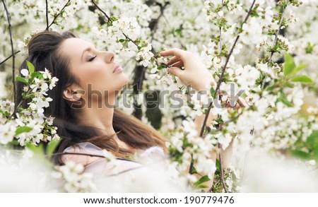 Beauty brunette in blooming garden - stock photo