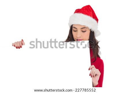Beauty brunette in santa hat showing white poster on white background