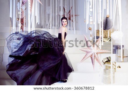 Beauty Brunette model woman holiday make up. Elegant girl in a black dress with very long train - stock photo