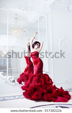 Beauty Brunette model woman in  evening red dress. Beautiful fashion luxury makeup and hairstyle,   full length with mirrors - stock photo